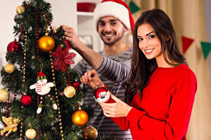 Обои Рождество Мужчины Шатенки Новогодняя ёлка Шар Улыбка Смотрит Руки девушка