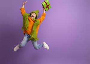 Фотографии Цветной фон Девочка Прыжок Подарков Счастливые Свитер Рука Шарфом ребёнок