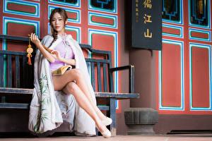 Фото Азиатка Скамейка Сидя Ноги Платья Шатенка Взгляд молодая женщина