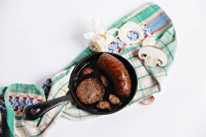 Фотографии Мясные продукты Сосиска Грибы Чеснок Шампиньоны двуспоровые Белом фоне Сковорода Пища
