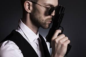 Картинки Мужчина Пистолет Сером фоне Сбоку Очков Рука Бородой