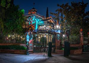 Картинки США Диснейленд Парк Здания Калифорния Анахайм Забором Дизайна Ночь Уличные фонари Дерево Ворота Природа
