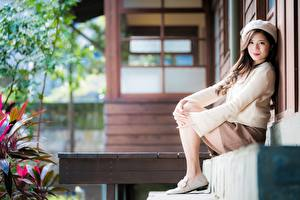 Фото Азиаты Размытый фон Сидит Юбки Свитер Берет Шатенки Смотрит молодая женщина