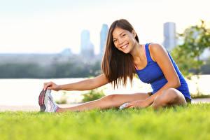 Фотография Азиаты Фитнес Траве Шатенка Улыбка Сидя Растяжка упражнение молодая женщина