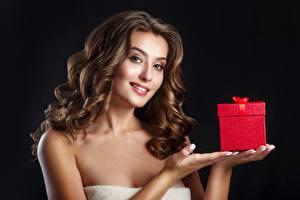 Фотография На черном фоне Рука Коробки Подарок Шатенки Смотрит Прически Волос