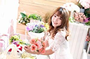 Картинка Букеты Азиаты Улыбка Милый Шатенки Взгляд молодая женщина Цветы