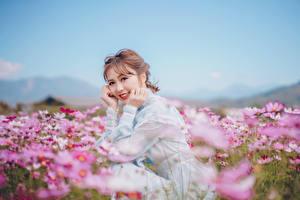Обои Луга Азиатки Боке Сидящие Платья Рука Улыбается Миленькие Шатенки Смотрит девушка Природа Цветы