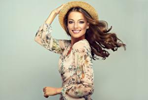 Обои Сером фоне Шатенки Улыбка Взгляд Шляпы Руки Фотомодель Волосы молодая женщина