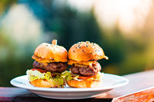 Фотография Гамбургер Булочки Быстрое питание Котлеты Размытый фон Тарелка