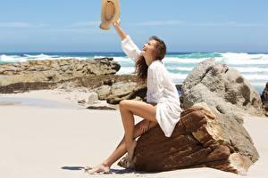 Фото Камни Море Лето Песок Сидит Ноги Шляпа Счастливые Релакс Шатенка девушка