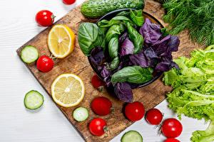 Фотографии Овощи Лимоны Томаты Огурцы Разделочная доска Продукты питания