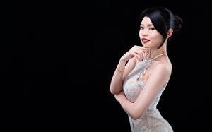 Картинки Азиатки На черном фоне Позирует Платья Рука Брюнетки Смотрит девушка