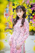 Фото Азиатка Размытый фон Платье Рука Шатенка Миленькие Смотрит молодая женщина