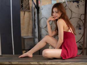 Картинки Азиаты Сидит Платье Ног Улыбается Шатенка Милая молодая женщина