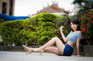 Фотографии Азиатки Сидящие Ног Шорт Улыбается Брюнетки Позирует девушка