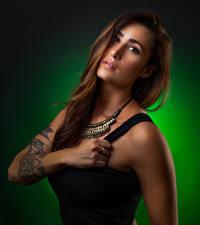 Фотографии Цветной фон Майке Руки Татуировки Шатенки Взгляд молодая женщина