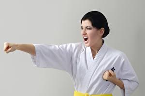Картинки Сером фоне Серый фон Руки Кричит Униформе Униформа Удар Karate Девушки