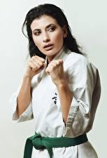 Картинка Сером фоне Униформе Брюнетки Смотрит Рука Поза Karate Девушки