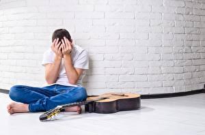 Картинки Мужчины Стены Кирпичный Сидит Джинсов Футболка Руки С гитарой Грустный переживание