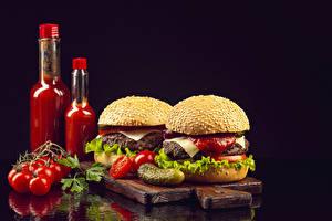 Фотографии Помидоры Гамбургер Огурцы Булочки На черном фоне Бутылки Кетчуп Разделочная доска Пища