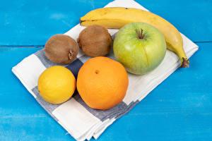 Фотографии Полотенце Бананы Киви Яблоки Лимоны Мандарины Цветной фон Еда