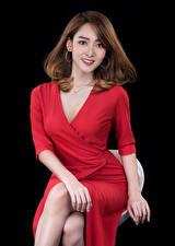 Картинки Азиаты Шатенка Платье Красный Сидящие Взгляд На черном фоне молодая женщина
