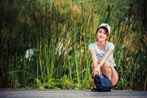 Картинка Азиатки Сумка Сидящие Футболке Бейсболка Смотрит девушка