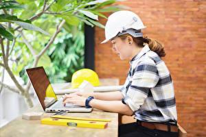 Картинка Работа Сидя Шлема Ноутбук Сбоку construction helmet Девушки