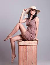 Фотографии Брюнетка Платья Красивый Ноги Поза Сидящие Шляпа Девушки