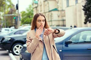 Фотографии Наручные часы Шатенка Пальто Смотрят Удивлена Рука Боится молодые женщины