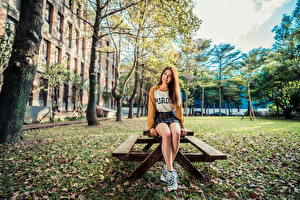 Фотография Азиатки Шатенки Стола Сидящие Ног Улыбается Смотрит девушка