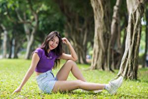 Картинки Азиаты Трава Сидя Ног Шорт Футболке Улыбается Смотрят молодая женщина
