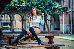 Картинки Азиаты Сидит Ноги Сапогах Взгляд Размытый фон Стола Красивая молодые женщины