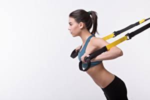 Фото Фитнес Брюнеток Тренируется Сером фоне спортивный Девушки