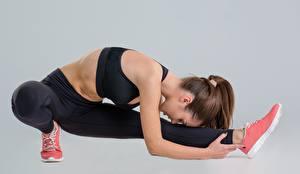 Фотография Фитнес Растяжка упражнение Ног Позирует Сером фоне Девушки