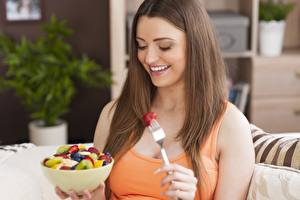 Фото Фрукты Шатенка Улыбается Здоровое питание Диета Миска Вилка столовая молодая женщина Еда