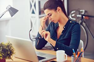 Фотографии Шатенки Офис Стол Сидящие Ноутбуки Очки fatigue молодая женщина Компьютеры