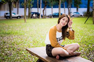 Фото Азиатки Жесты Сидящие Ног Улыбается девушка