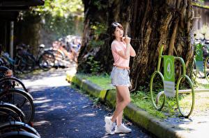 Фотографии Азиаты Поза Ноги Футболке Рука Смотрит девушка