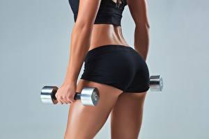 Картинка Фитнес Крупным планом Гантели Рука Ягодицы Сером фоне Шорты hips спортивные Девушки