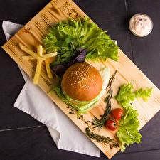 Обои Гамбургер Картофель фри Булочки Овощи Помидоры Разделочная доска
