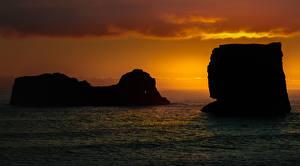 Картинки Исландия Море Рассвет и закат Скалы Dyrholaey Природа