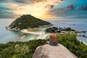 Картинка Таиланд Рассвет и закат Мужчина Остров Сидящие Кепке Утес Природа