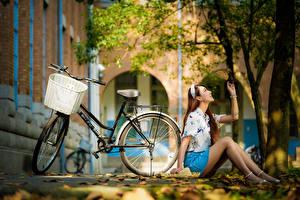 Фотография Азиатки Осенние Сидит Ног Юбка Блузка Листва Велосипеды Размытый фон девушка