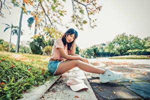 Фотографии Азиатки Брюнетки Сидящие Кроссовках Ног Шорт Футболке Смотрит Боке девушка