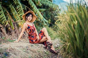 Фото Азиаты Брюнеток Сидит Платья Ног Шляпы Смотрят девушка