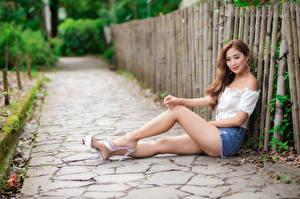 Фото Азиаты Сидящие Ног Шорты Блузка Смотрит Размытый фон молодая женщина