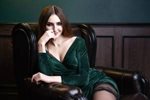 Обои для рабочего стола Шатенки Кресло Сидит Платья Декольте Улыбается Смотрит Denis Kornilov молодые женщины