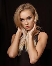 Картинки Блондинки Фотомодель Рука Волос Смотрит На черном фоне Красивая Evelina