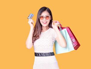 Фотография Сумка Покупки Шатенки Очки Улыбается Руки Цветной фон Бумажный пакет молодая женщина